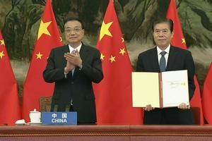 El primer ministro de China, Li Keqiang, aplaude mientras su ministro de Comercio, Zhong Shan, muestra el documento del acuerdo comercial RCEP.