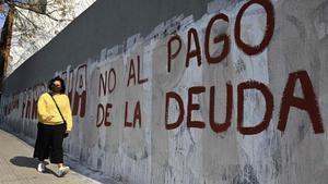 Una mujer camina junto a una pintada que insta a no pagar la deuda, el lunes en Buenos Aires.