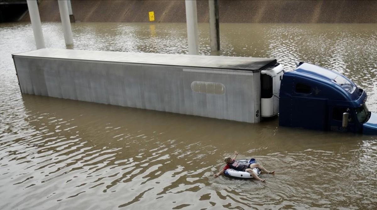 Un camión de gran tonelaje se mantiene bloqueado por el agua en Houston, mientras un vecino avanza sobreun gran flotador.