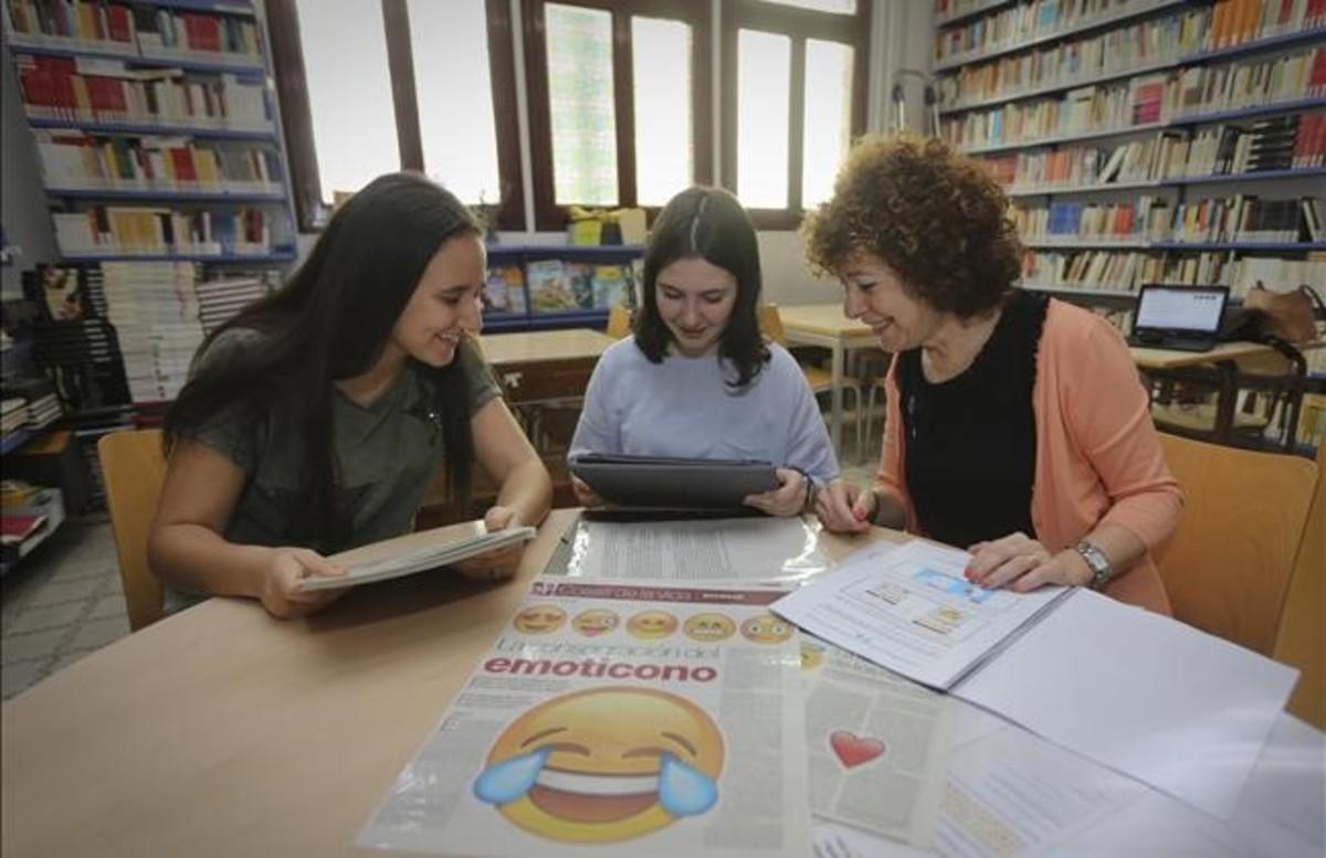 Salma Zian (a la izda.), Cristina Manzanares y la profesora María del Pilar Menoyo, con la portada que inspiró su trabajo de investigación, en la biblioteca del instituto Juan Manuel Zafra de Barcelona.