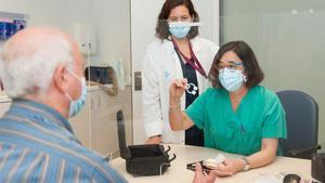 Profesionales del Hospital de Bellvitge informan a un paciente sobre el uso de la espirometría a domicilio.