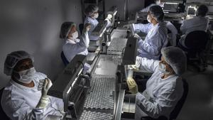 Empleados trabajan en la línea de producción de una vacuna contra el coronavirus covid-19