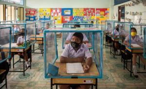 Escolares tailandeses con mascarilla y aislados en 'celdas' de plástico.