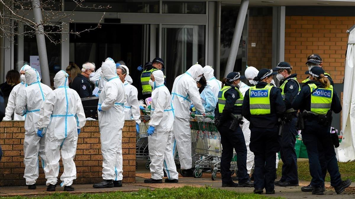 Los bomberos vestidos con equipo de protección personal se preparan para distribuir alimentos en una torre de viviendas públicas en el norte de Melbourne, Australia.
