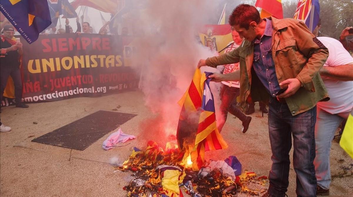Varios manifestantes de la marcha ultra del 12-O en Barcelona queman una 'estelada'.