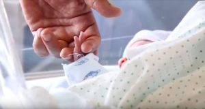 Un bebé recién nacido coge la mano de uno de sus padres.