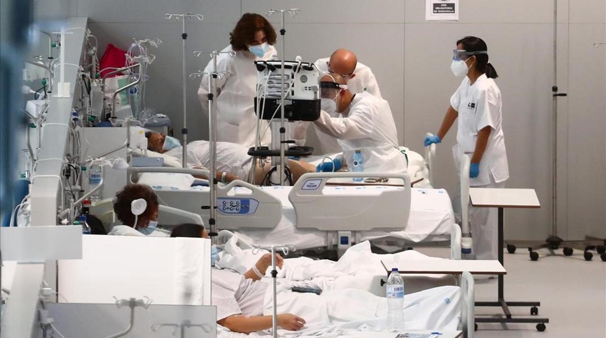Unos doctores atienden este lunes a un paciente con coronavirus en el Hospital Enfermera Isabel Zendal en Madrid.