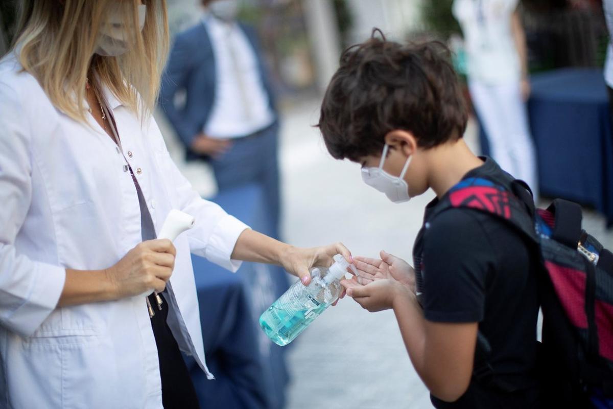 Un niño se desinfecta las manos después de que le tomen la temperatura a la entrada del colegio