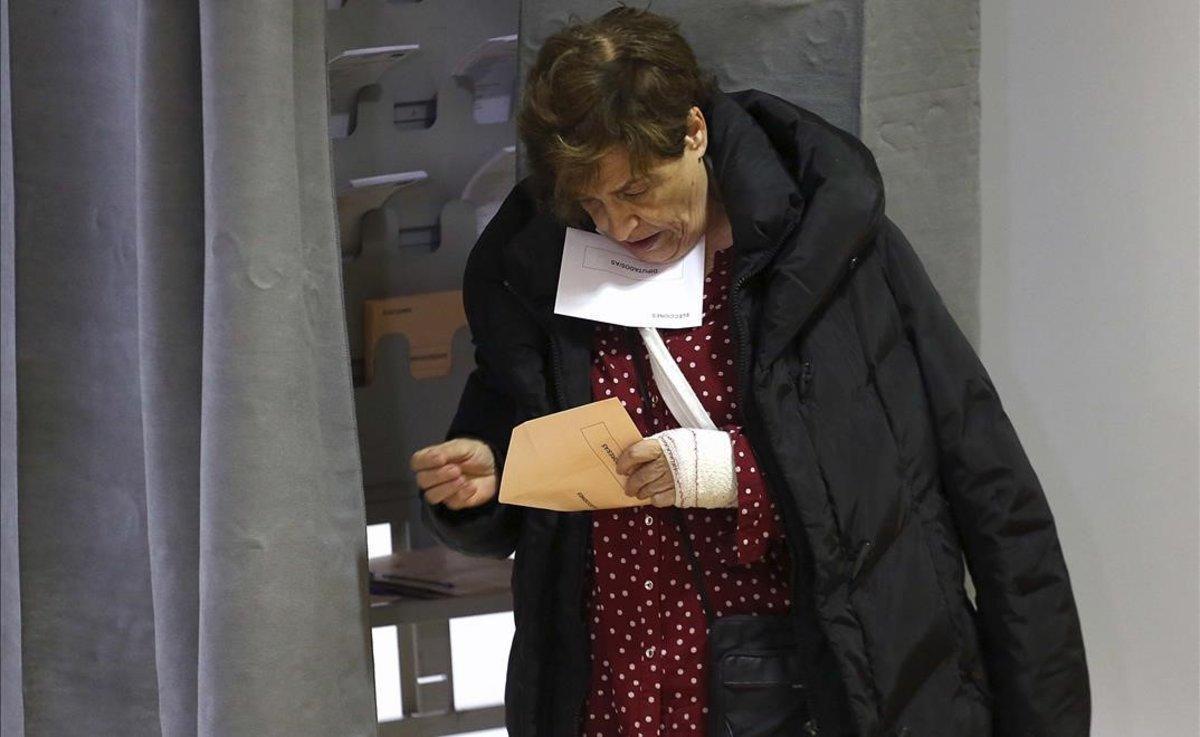 Una mujer sostiene su voto, en un colegio electoral de Madrid.
