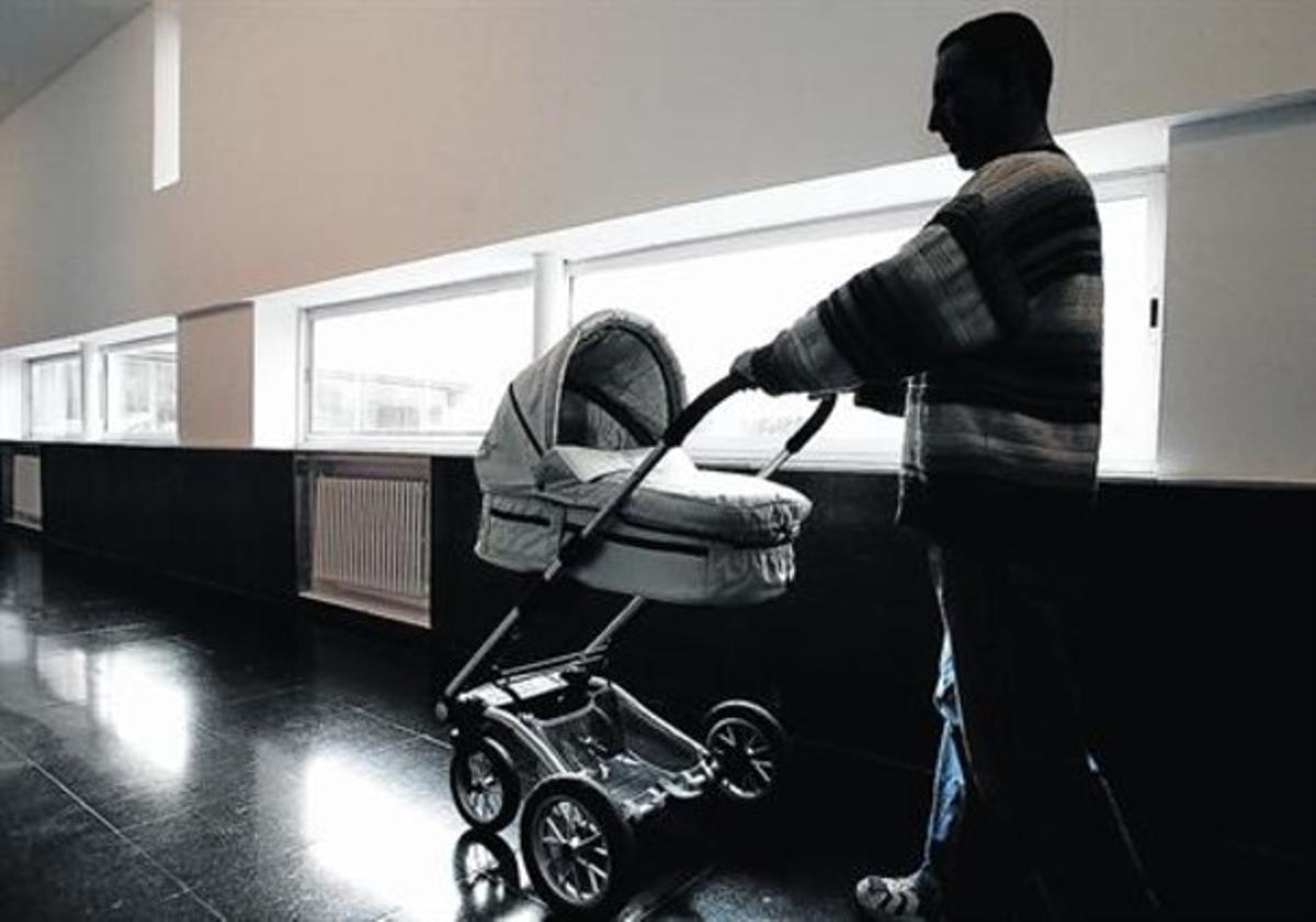 Un hombre pasea a su bebé en un cochecito en Barcelona.