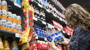 Una joven observa la etiqueta de un refresco en un supermercado