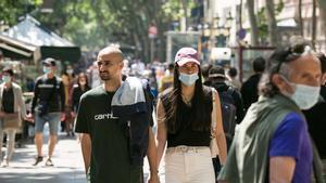 Gente con y sin mascarilla, por la Rambla de Barcelona.