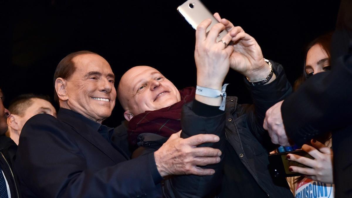 Berlusconi (izquierda) posa para un selfi con un seguidor de Forza Italia, en Milán, el 25 de febrero.