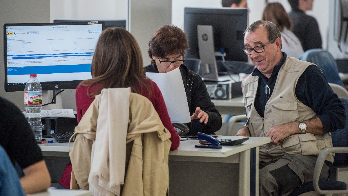 Contribuyentes realizando la declaración de la renta con un técnico de Hacienda