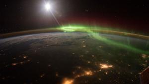 Foto de la Tierra de noche con luces verdes y rojas de una aurora boreal, tomada desde el espacio por el astronauta Scott Kelly, en 2016.