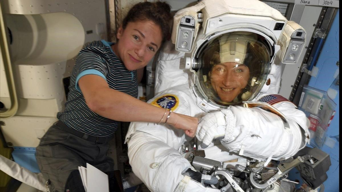 Christina Koch, a la derecha, y Jessica Meir, con traje de astronauta, en la estación espacial internacional.