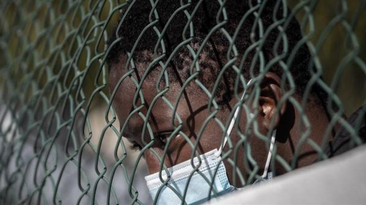 Un migrante apoyado en la valla del campamento de Las Canteras.