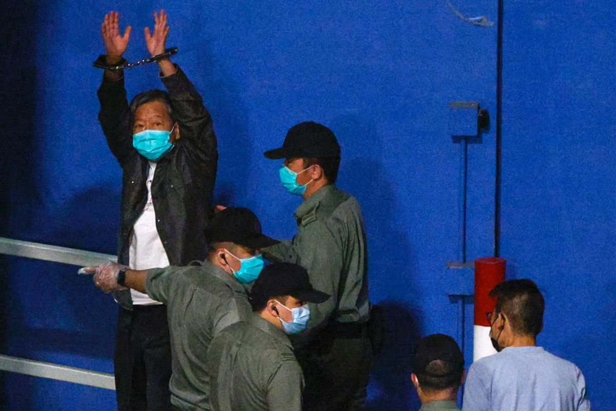 El activista hongkonés Lee Cheuk-yan levanta sus manos al llegar a la prisión donde cumplirá condena.