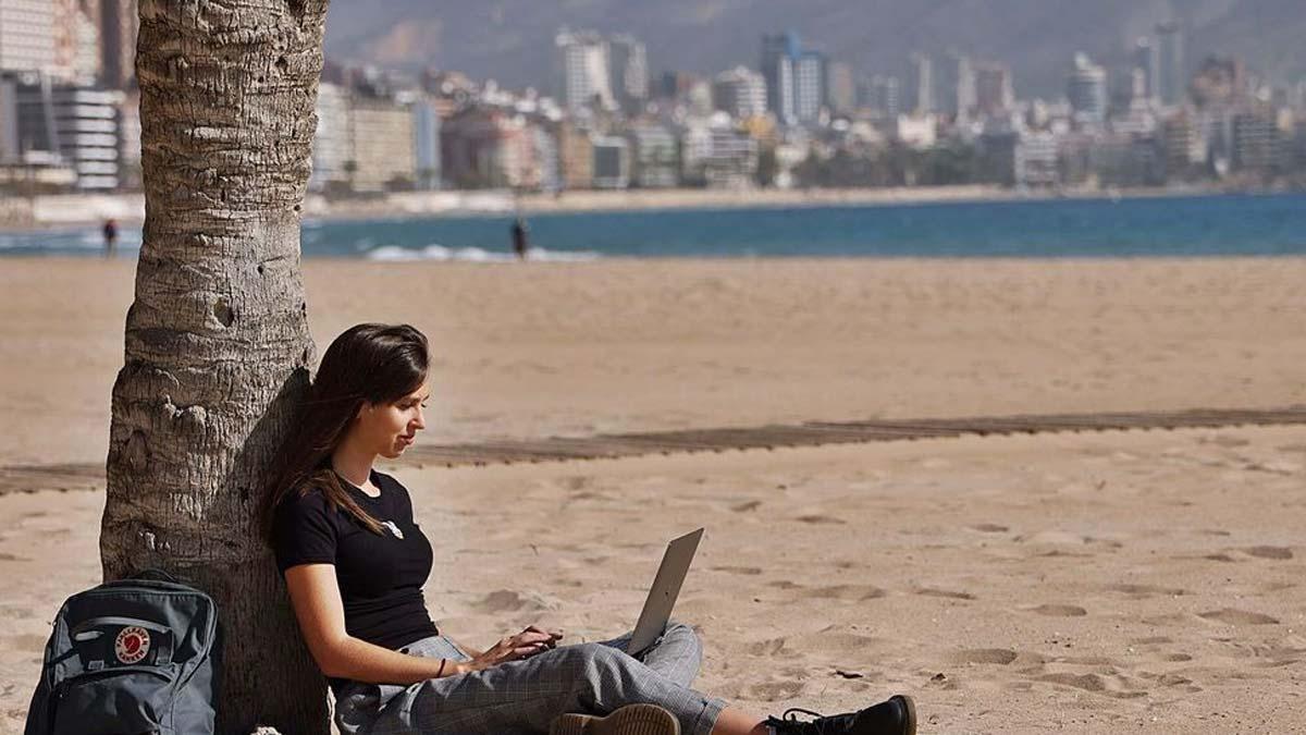 Una joven inglesa trabaja desde la playa de Benidorm con su ordenador, una de las posibilidades que tienen los «nómadas digitales».