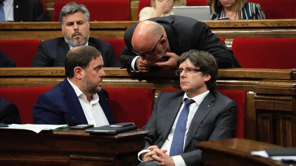 Puigdemont, Junqueras y Coromines hablando en el hemiciclo