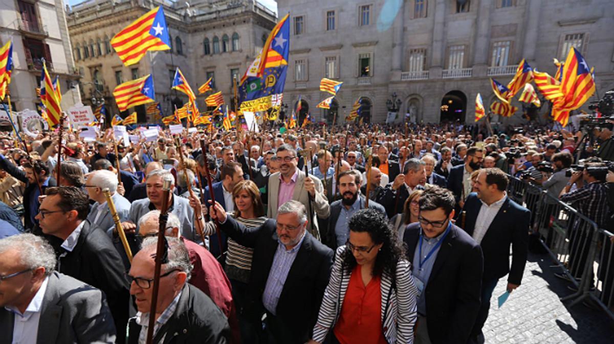 Los alcaldes y resto de autoridades cruzan la plaza Sant Jaume desde el ayuntamiento al Palau de la Generalitat.