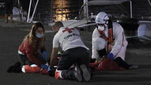 Miembros de Cruz Roja auxilian a algunos de los migrantes de una patera rescatada cerca de Gran Canaria.