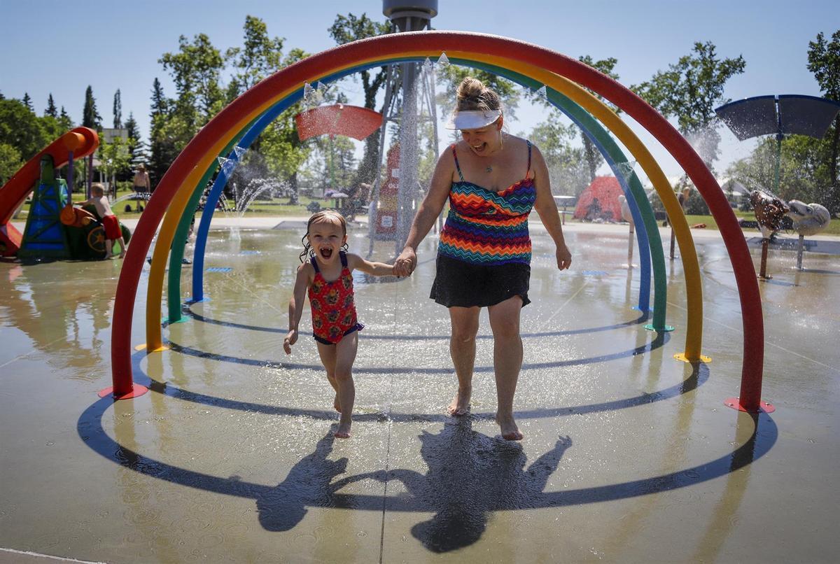 Una madre y su hija corren entre aspersores para tratar de vencer el calor en un parque.