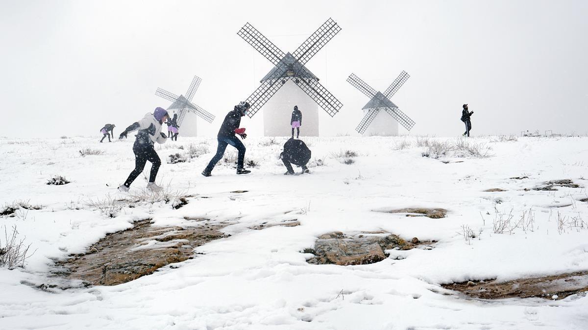 Un grupo de jóvenes juega junto a los molinos de Campo de Criptana (Ciudad Real).