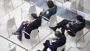 Diputados consultando sus teléfonos móviles en el Parlament, durante el debate de investidura de Pere Aragonès.
