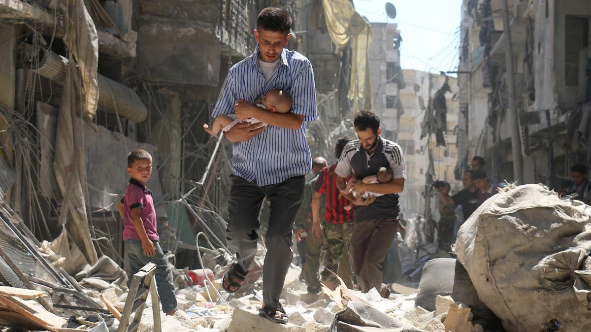 Hombres sirios llevan bebés a través de los escombros de edificios destruidos tras el ataque aéreo en el barrio de Salihin, controlado por los rebeldes en la ciudad norteña de Alepo, el 11 de septiembre de 2016.