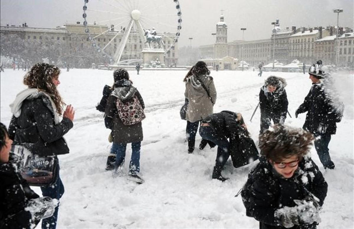 Niños jugando en la nieve en la plaza Bellecour de Lyon (Francia).