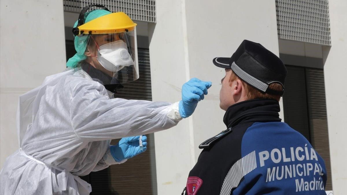 Un sanitarioefectuando las pruebas para detectar el coronavirus a un policiaMunicipal de Madrid.