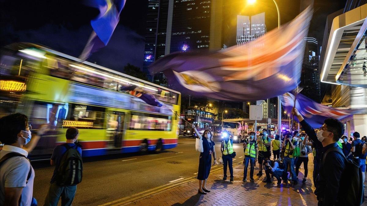 Manifestantes antigubernamentales ondean la vieja bandera colonial durante una vigilia en Hong Kong, este viernes.