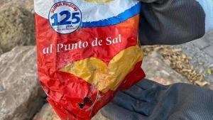 Hallan en las rocas del Postiguet una bolsa de patatas de más de 22 años.