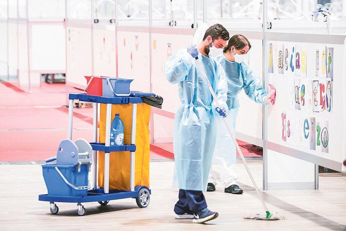 Dos trabajadores del equipo de limpieza de los pabellones 7 y 9 del hospital de campaña del recinto ferial Ifema.