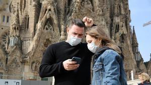 Dos turistas con mascarilla frente el templo de la Sagrada Família, a mediados de marzo, antes del confinamiento.