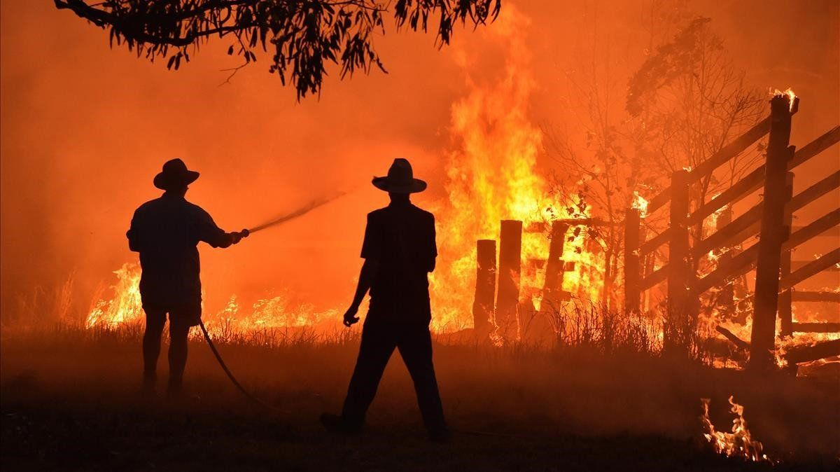 Vecinos de Hillsville, a unos 350 kilómetros de Sydney, intentan proteger su propiedad dentro en una de las recientes oleadas de incendios que ha sufrido Australia.