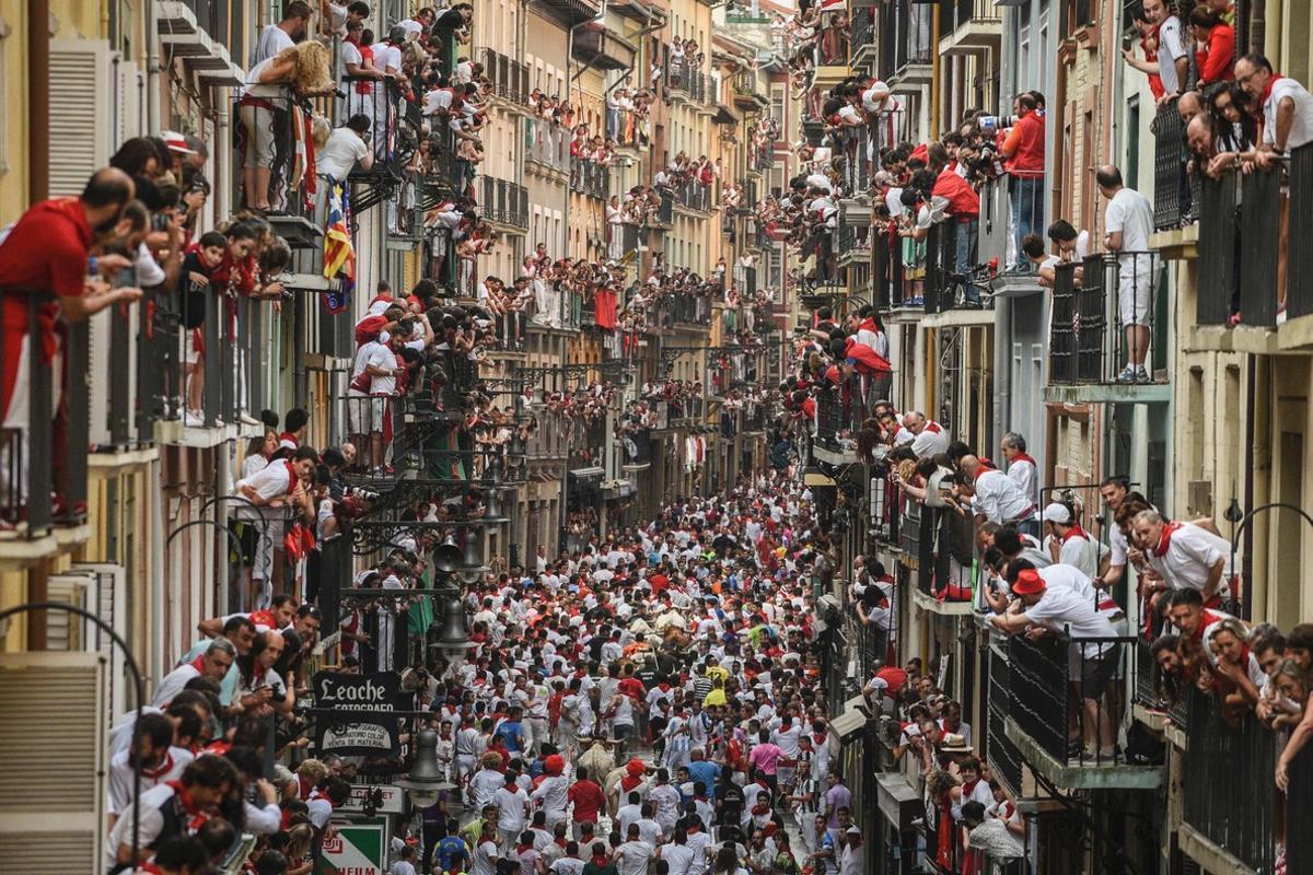 Balcones abarrotados de gente siguiendo el cuarto encierro de San Fermín, este domingo.