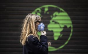 Una mujer protegida con una mascarilla pasa ante una publicidad comercial.
