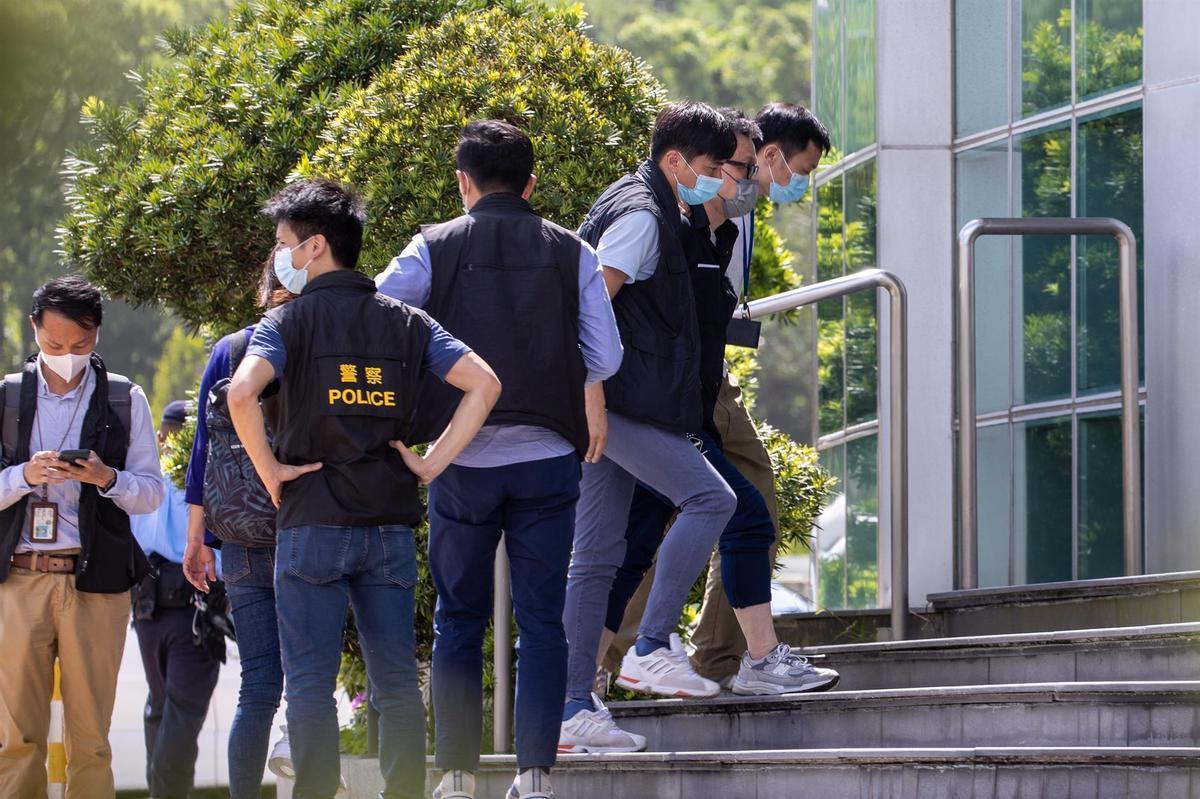 Cheung Chi Wai, del Apple Daily, esposado y escoltado por la policía de Hong Kong.