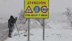 Un cámara de televisión graba el estado de una carretera durante una tormenta de nieve.