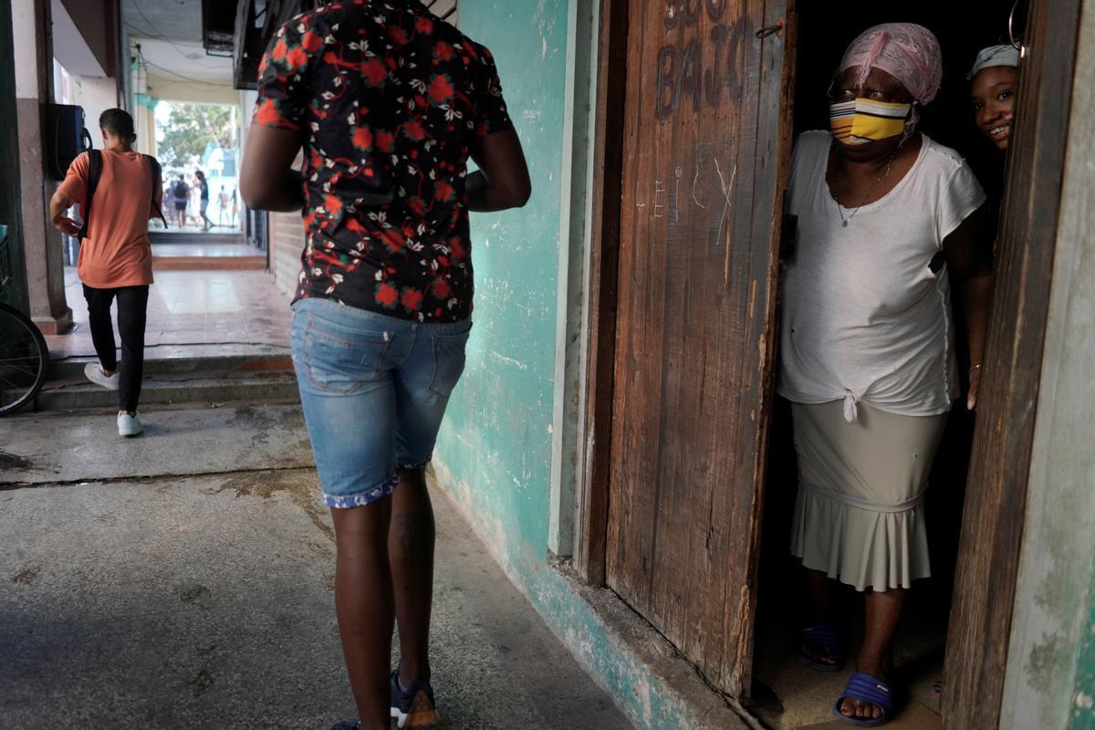 Una mujer mira desde la puerta en La Habana.