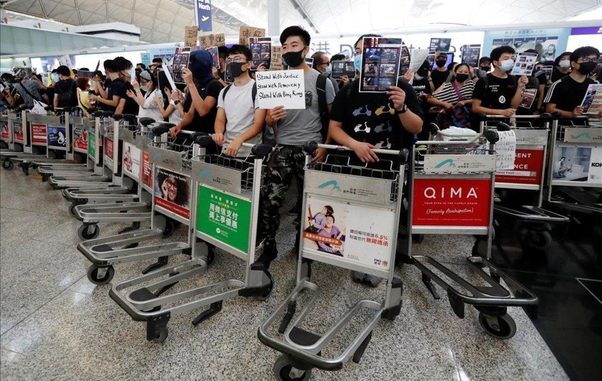 Manifestantes usan carritos para hacer barricadas frente a las puertas de acceso en el aeropuerto de Hong Kong.