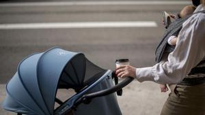 Una mujer con mascarilla consulta el móvil con su bebé a cuestas, el pasado 31 de agosto.