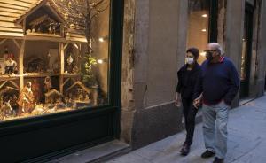 Una pareja con mascarilla pasea por el centro de Barcelona, frente a un establecimiento con motivos navideños.