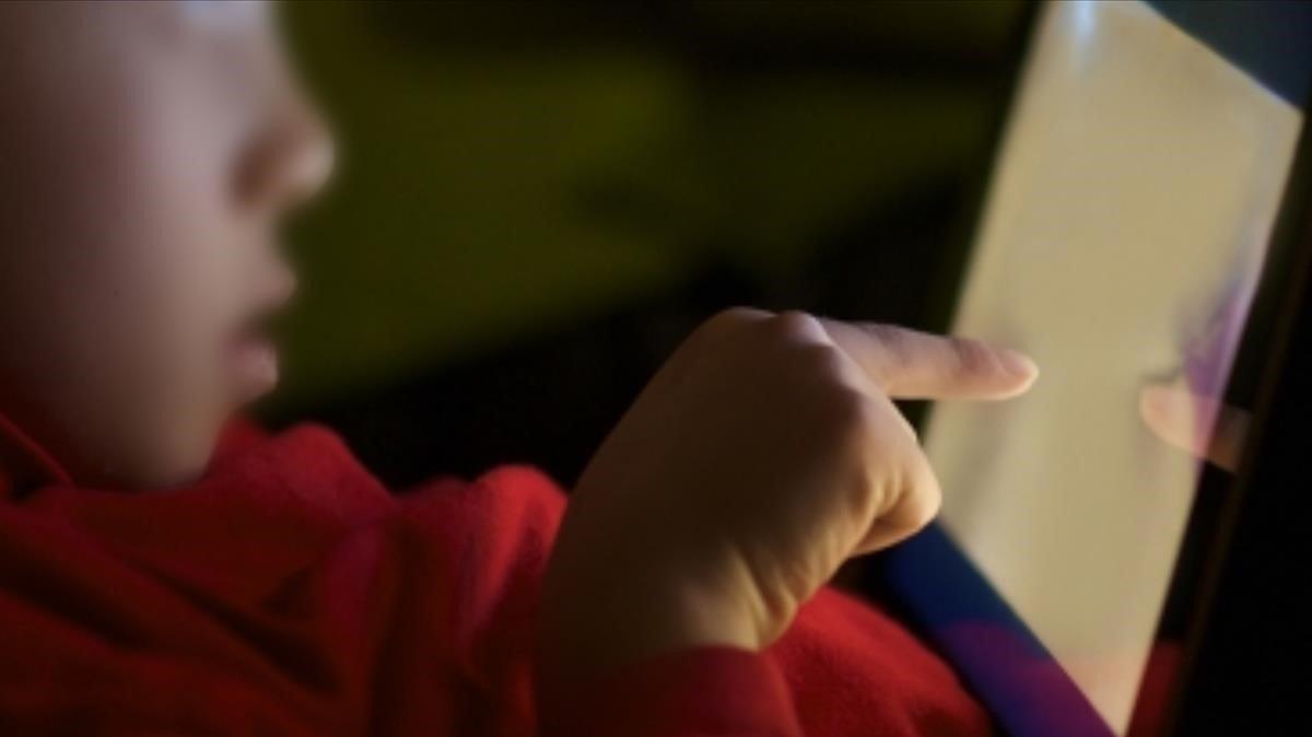 Un menor, utilizando una tableta en casa.