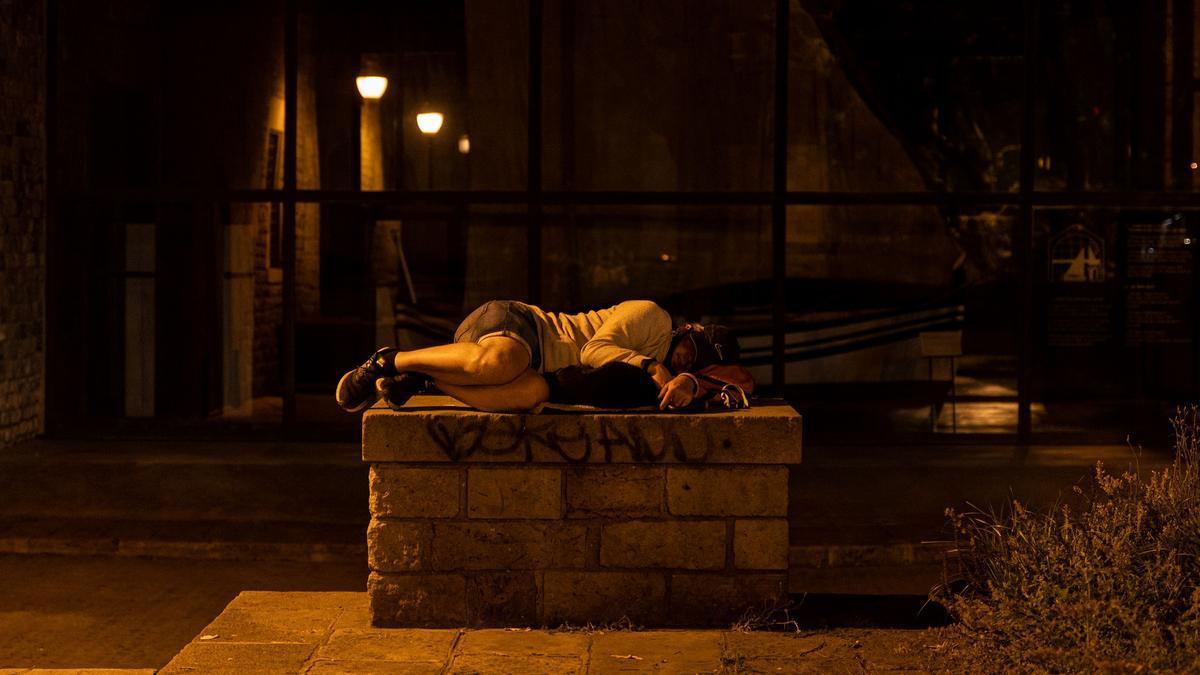 Una persona sin hogar duerme en los alrededores del Museo Marítimo