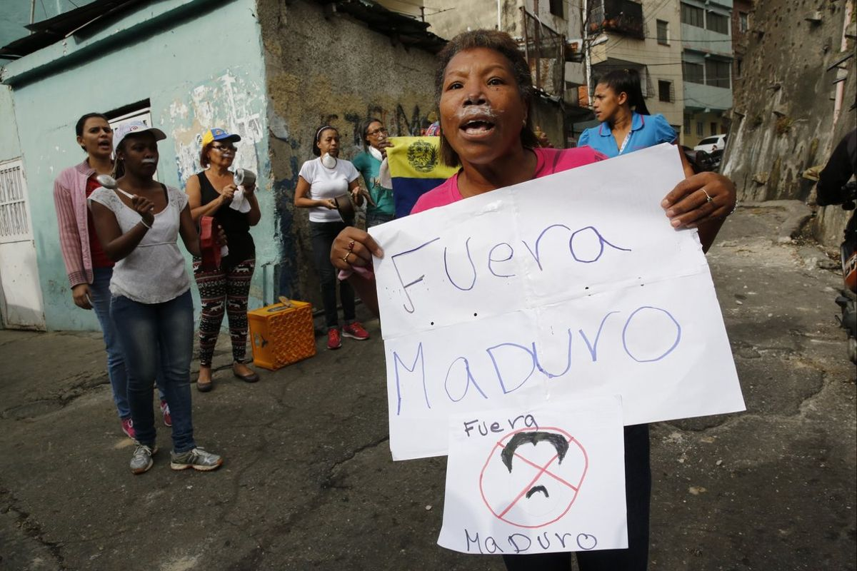 A woman with toothpaste under her nose to help with the effects of tear gas fired by security forces holds a sign that reads in SpanishGet out Maduroreferring to Venezuelan President Nicolas Maduroin the Cotiza neighborhood of CaracasSecurity forces have fired tear gas against protesters in a poor neighborhood near the presidential palace after an apparent uprising by a national guard unitAP Photo Ariana Cubillos