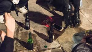 Unos jóvenes hacen botellónen la vía pública.