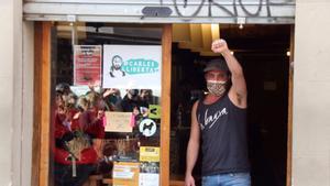 Carles, en la entrada de su taberna, saluda a los manifestantes, en Sants